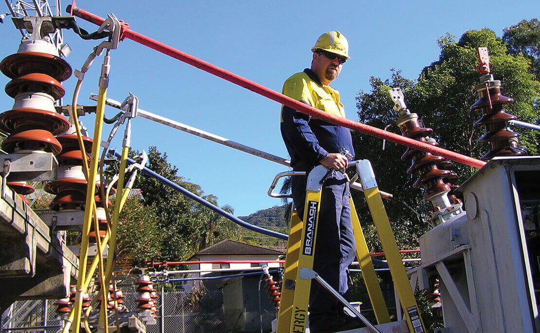 Close up of electrical worker using the fibreglass WorkMaster 550mm Step Platform ladder at an electrical substation.