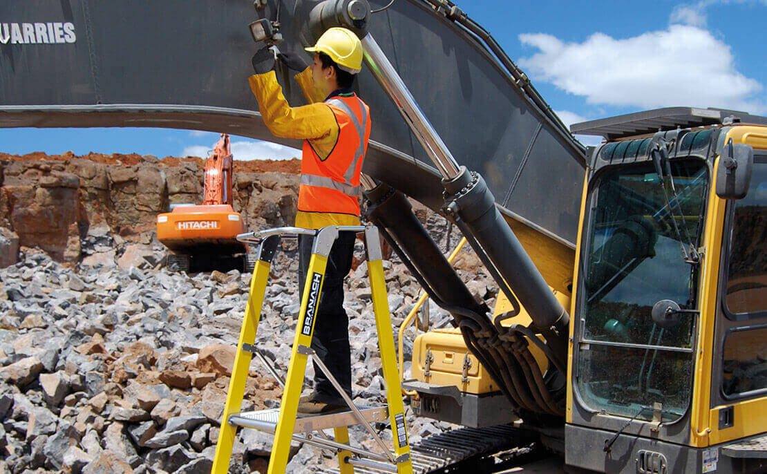 Mining worker using the fibreglass WorkMaster 550mm Step Platform ladder to inspect machinery at a mining site.