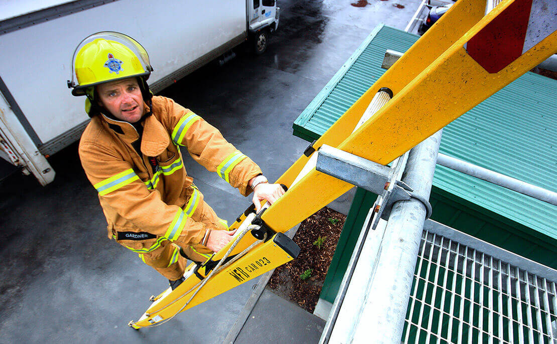 A firefighter climbing the fibreglass PowerMaster Extension ladder.