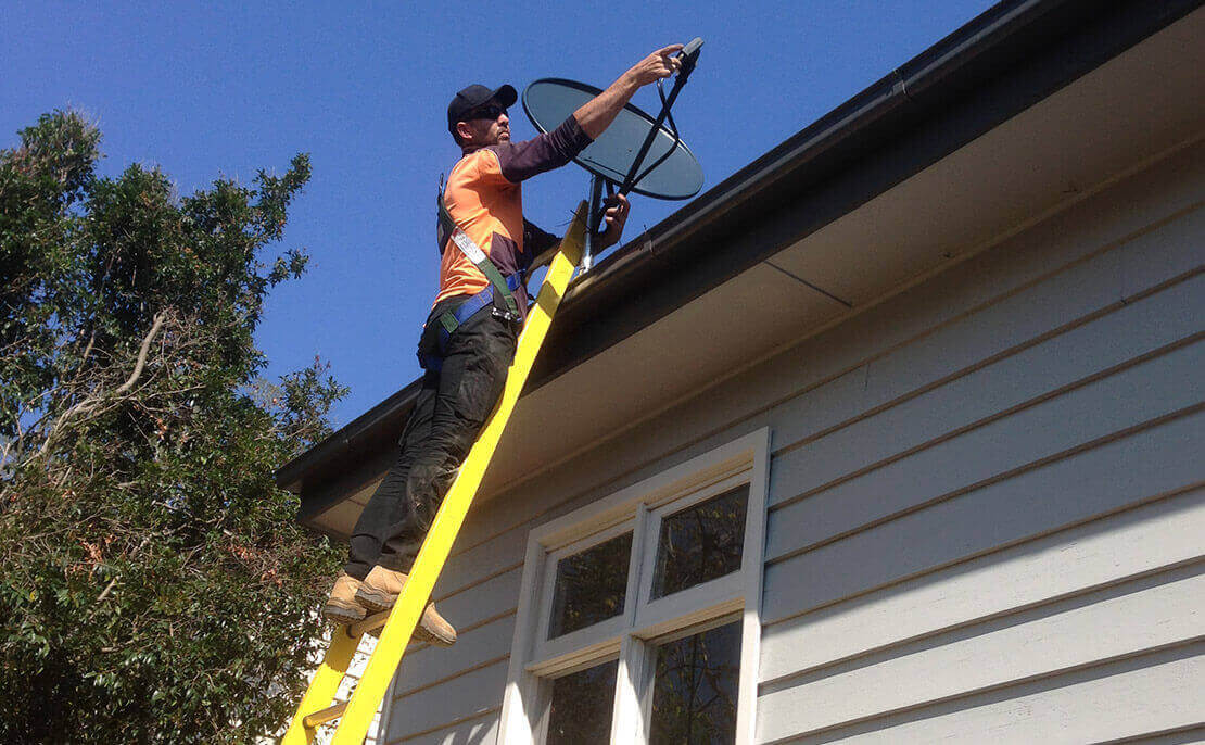 Telecommunications worker using the fibreglass PowerMaster Extension ladder to install a a satellite dish.