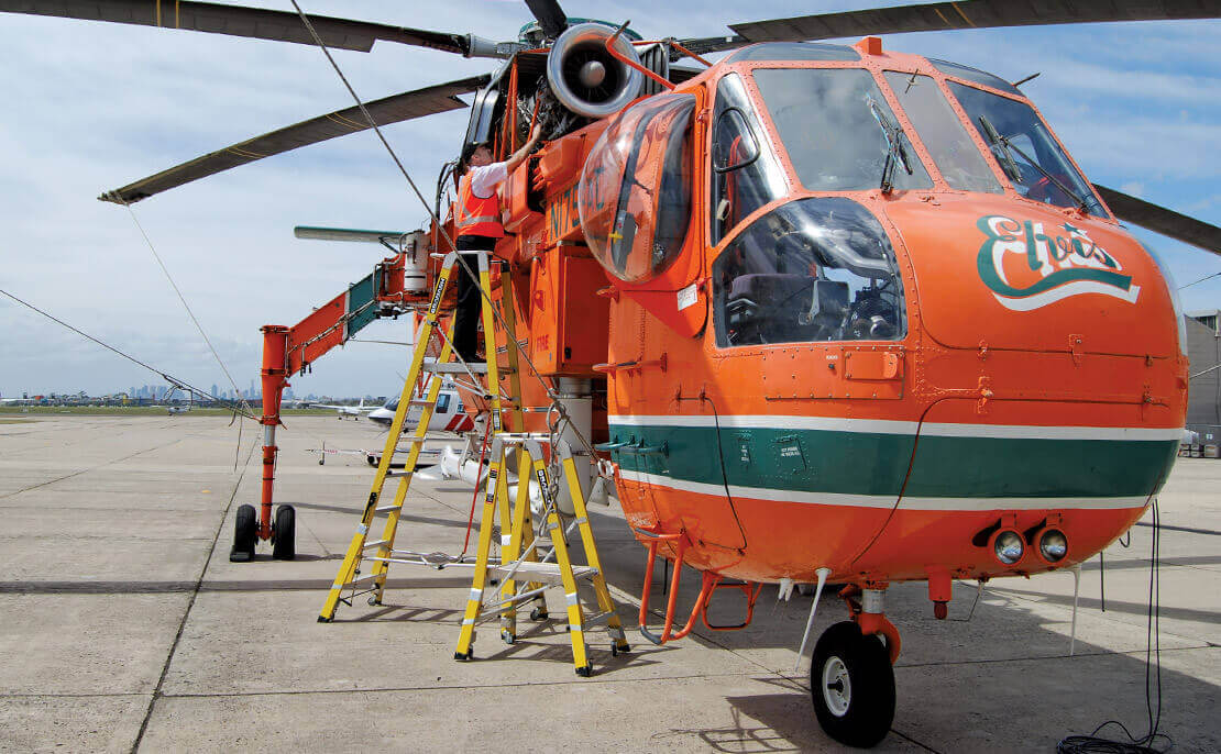A small and large fibreglass WorkMaster 550mm Step Platform ladder in front of the 'Elvis' helicopter, with a worker inspecting the top of the helicopter.