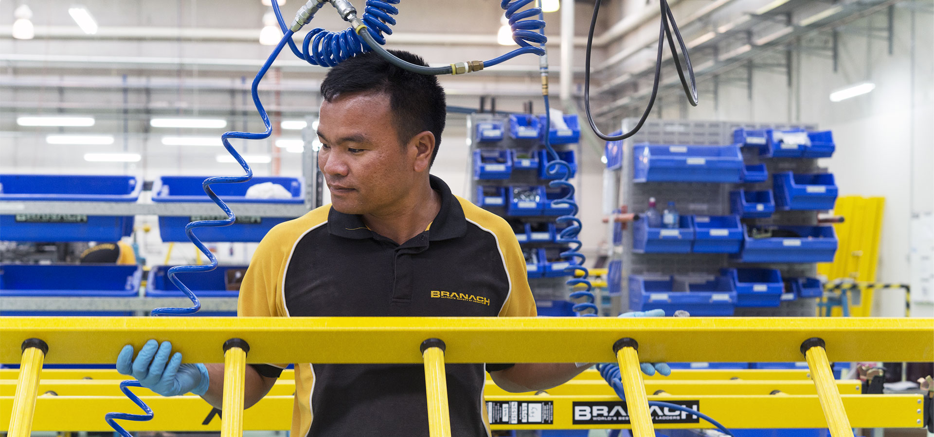 Branach staff member holding a fibreglass PowerMaster Single ladder in the factory.