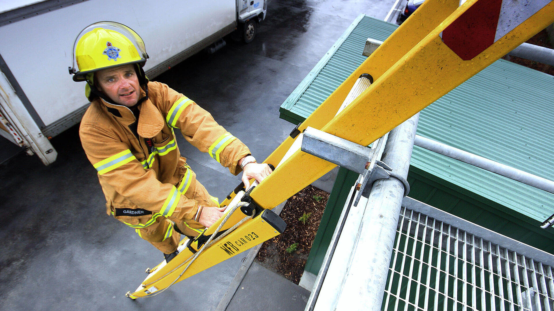 A fireman climbing up a Branach fibreglass PowerMaster Extension ladder.