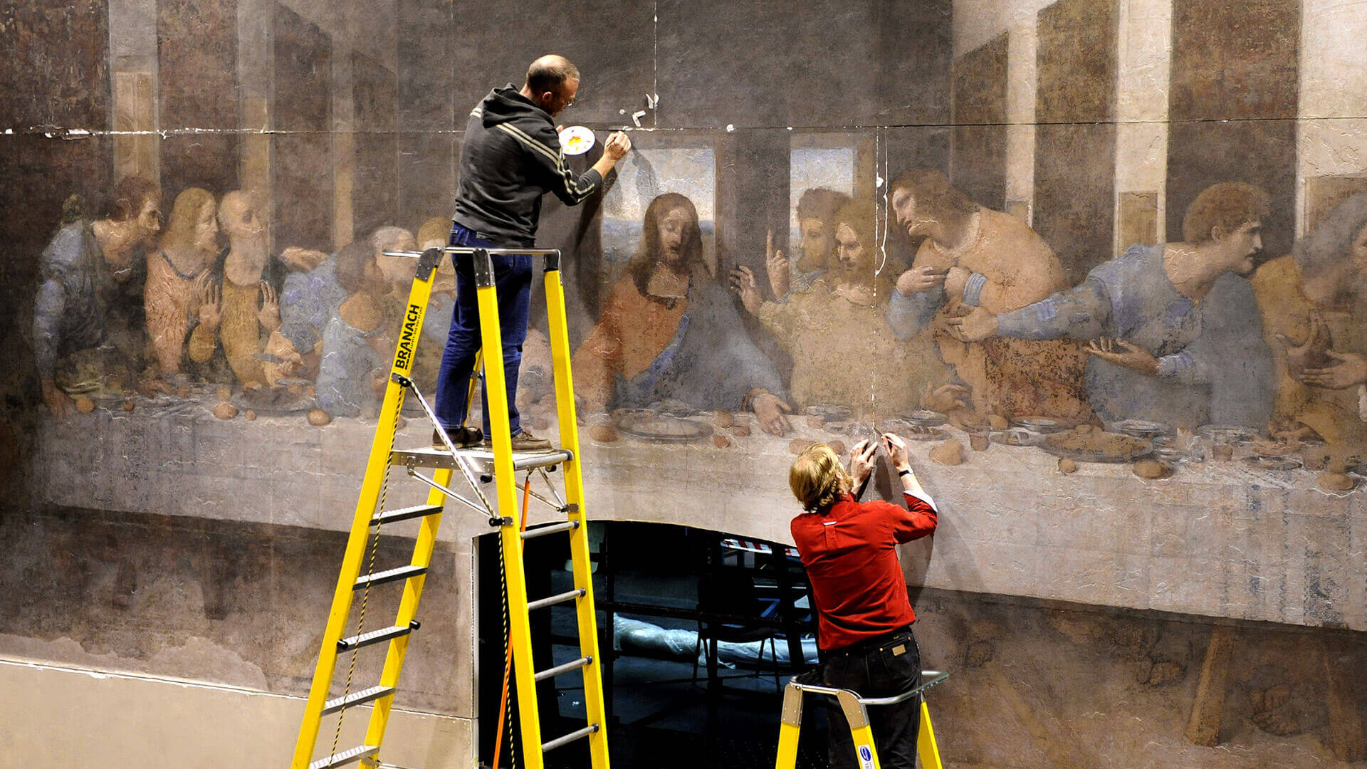Two people on Branach's fibreglass WorkMaster 450mm Safety Step Platform ladders touching up a painting of The Last Supper.