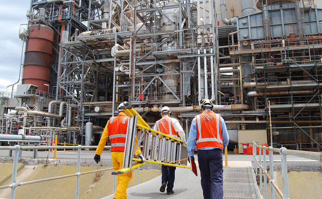3 Oil and Gas workers walking into an oil refinery, carring a closed fibreglass WorkMaster 550mm Step Platform ladder.