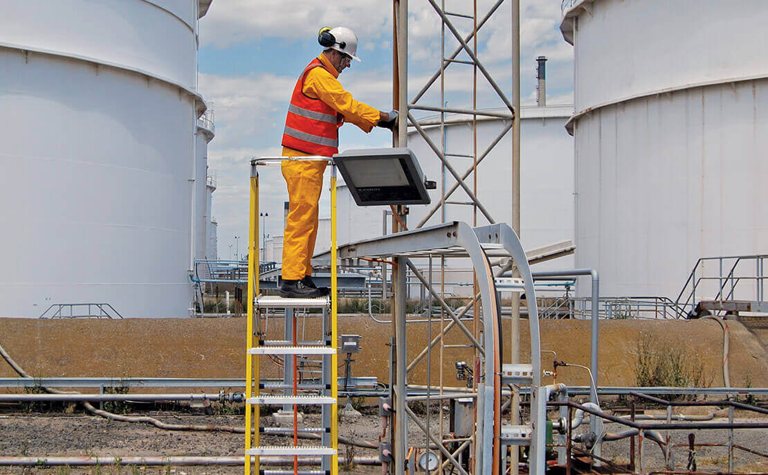 An Oil and Gas worker standing on the platform of a fibreglass WorkMaster 550mm Step Platform ladder to carry out inspections.