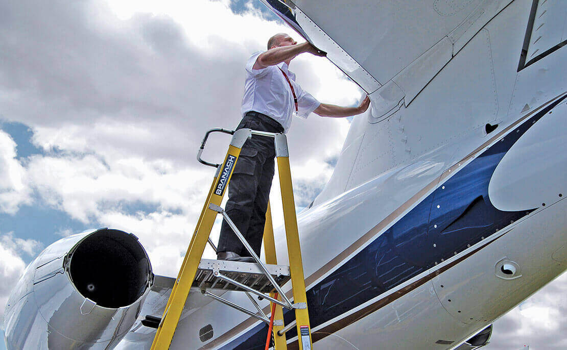 Transport worker using the fibreglass WorkMaster 550mm Step Platform ladder to inspect the top of a small plane.